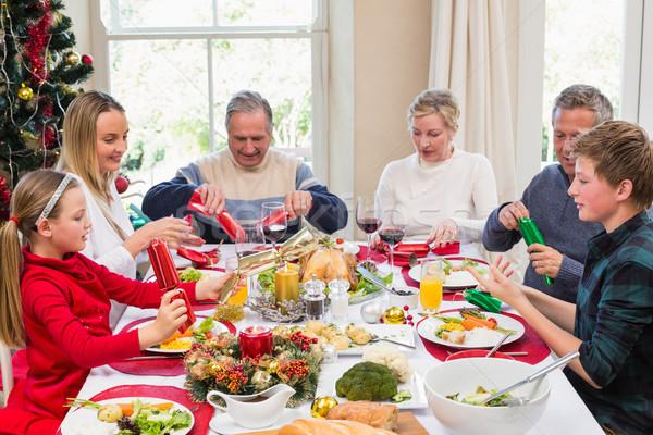 Family pulling christmas crackers at the dinner table Stock photo © wavebreak_media