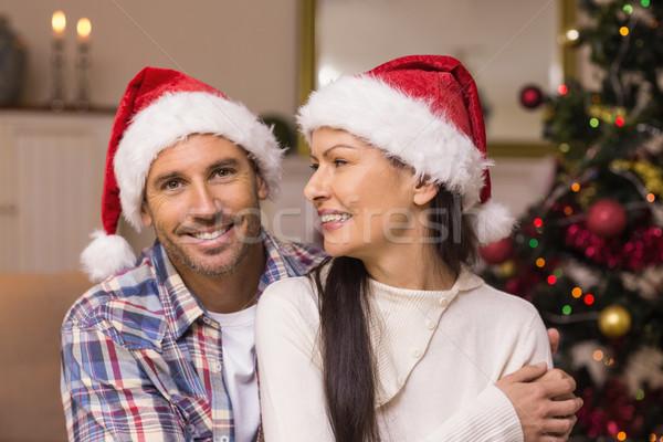 Festive couple in santa hat hugging on the couch Stock photo © wavebreak_media