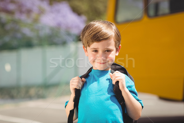 Cute pupil smiling at camera by the school bus Stock photo © wavebreak_media