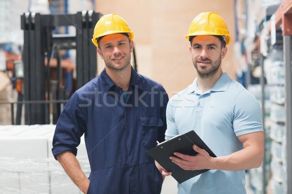 Sonriendo colega posando portapapeles almacén hombre Foto stock © wavebreak_media