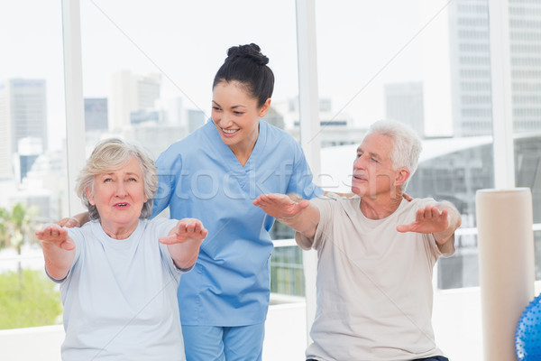 Trainer assisting senior couple to exercise Stock photo © wavebreak_media