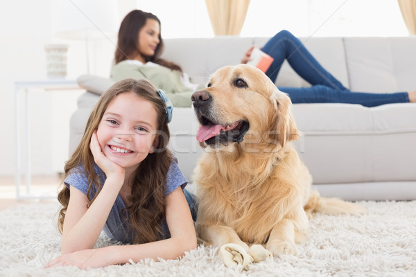 Girl with dog on rug while mother relaxing at home Stock photo © wavebreak_media