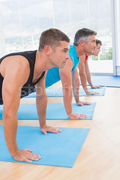 Group of men working on exercise mat  Stock photo © wavebreak_media