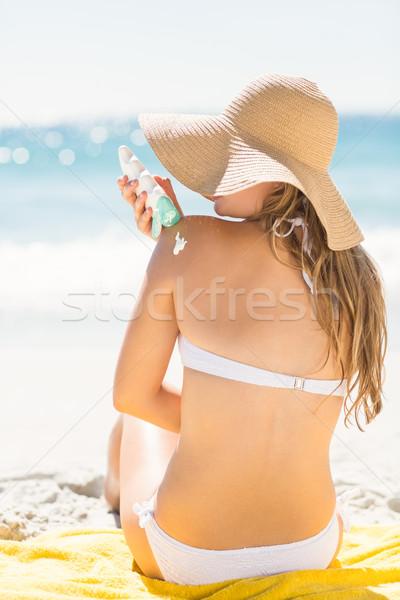 Pretty blonde woman putting sun tan lotion on her shoulder Stock photo © wavebreak_media