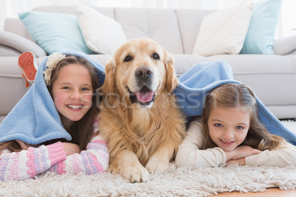 Sisters lying on rug with golden retriever under a blanket Stock photo © wavebreak_media
