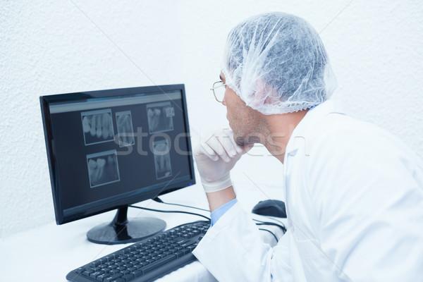 Dentist looking at x-ray on computer Stock photo © wavebreak_media