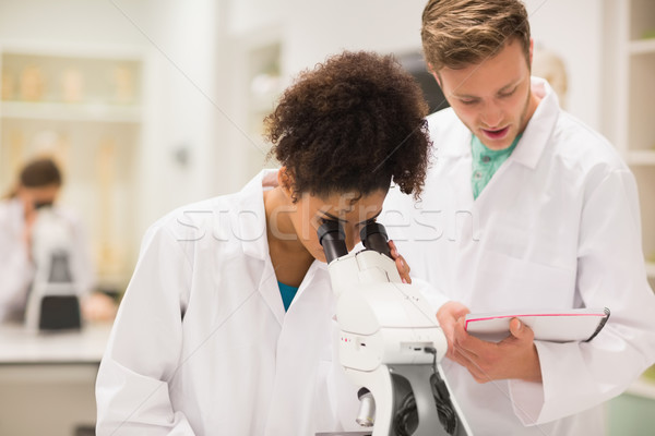 Medical students working with microscope Stock photo © wavebreak_media