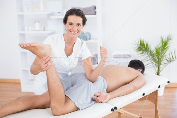 Physiotherapist doing leg massage and smiling at camera Stock photo © wavebreak_media