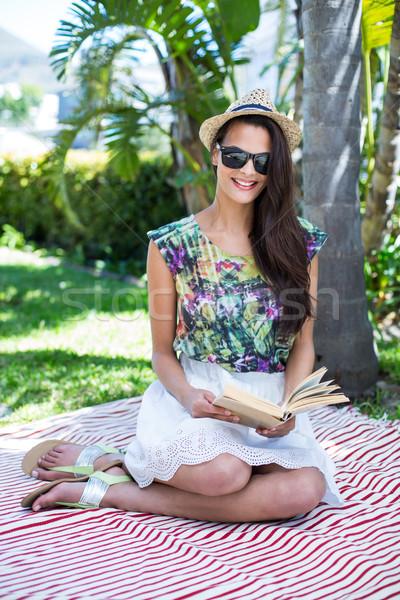 улыбаясь красивой брюнетка сидят чтение книга Сток-фото © wavebreak_media