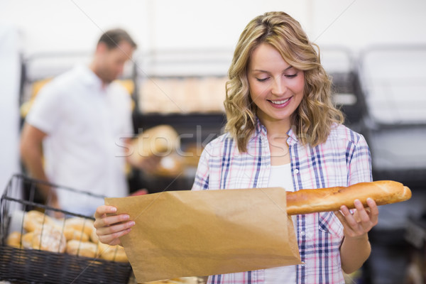 Smiling blonde woman looking at a bread  Stock photo © wavebreak_media