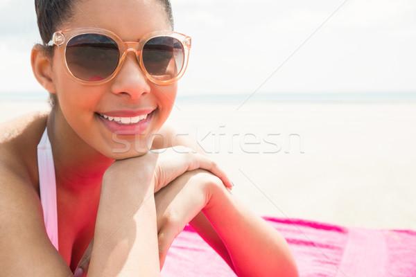 Mosolygó nő napozás törölköző tengerpart bikini női Stock fotó © wavebreak_media