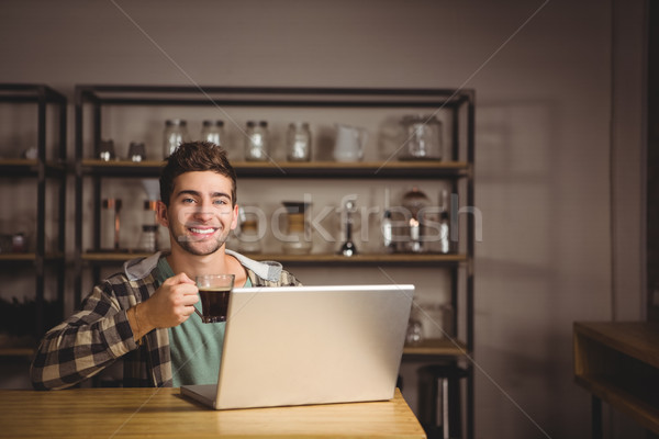 Smiling hipster drinking coffee and using laptop Stock photo © wavebreak_media