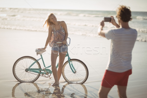 Stock photo: Smiling woman standing by bicycle while man photographing her at beach