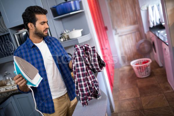 Homem ferro olhando camisas em pé Foto stock © wavebreak_media