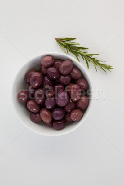 Overhead view of brown olives in bowl by herb Stock photo © wavebreak_media