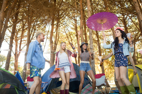 Low angle view of happy young friends dancing at campsite Stock photo © wavebreak_media