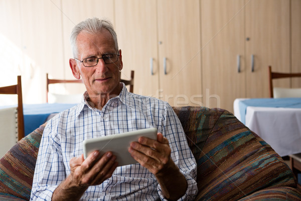 Senior man using tablet computer while sitting on armchair Stock photo © wavebreak_media