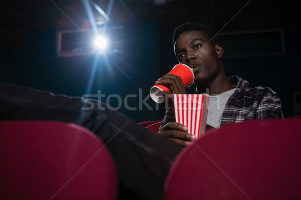 Man having cold drinks while watching movie in theatre Stock photo © wavebreak_media