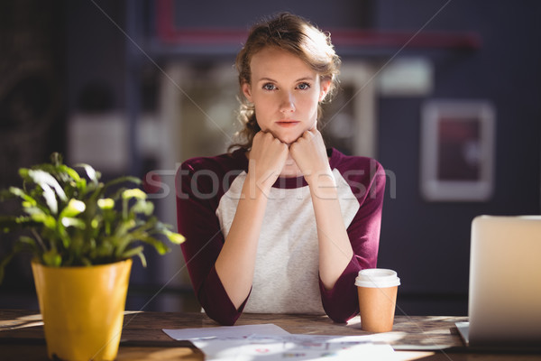 Portrait of confident young designer sitting with disposable coffee cup and sheets Stock photo © wavebreak_media