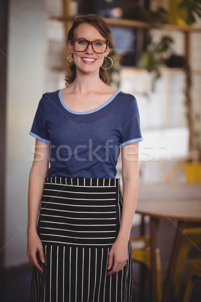 Portrait of smiling young waitress wearing eyeglasses at coffee shop Stock photo © wavebreak_media