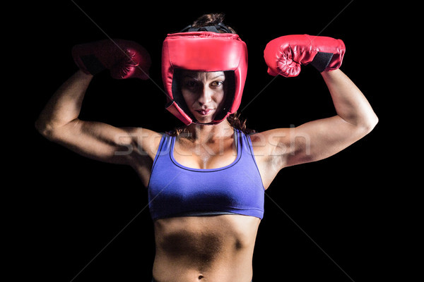 Portrait of confident female fighter flexing muscles Stock photo © wavebreak_media