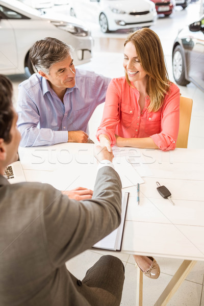 Stock photo: Smiling couple buying a new car