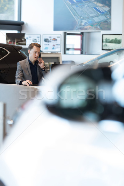 Stock photo: Car salesperson talking on landline phone in car showroom