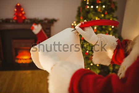 Santa claus sitting with stack of gift boxes in living room during christmas time Stock photo © wavebreak_media