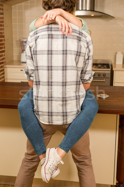 Cute couple cuddling with girlfriend sitting on the counter Stock photo © wavebreak_media