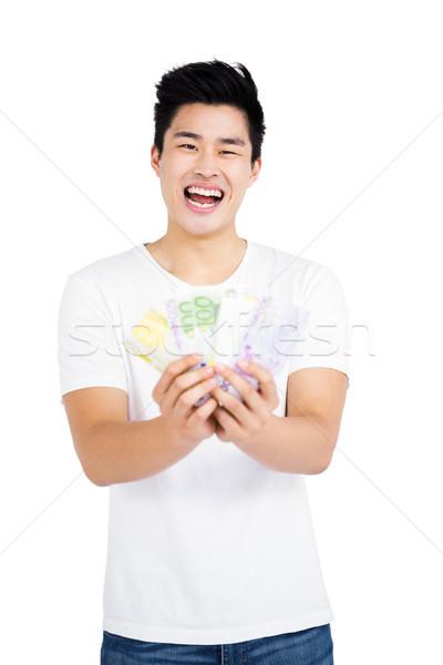 Jeune homme monnaie note portrait blanche Photo stock © wavebreak_media