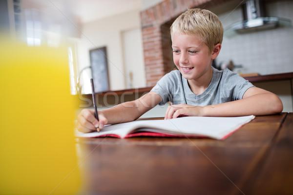 Uśmiechnięty chłopca praca domowa kuchnia domu tabeli Zdjęcia stock © wavebreak_media