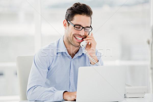 Zakenman praten telefoon met behulp van laptop kantoor computer Stockfoto © wavebreak_media