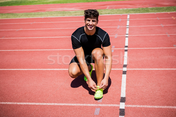 Portrait of male athlete tying her shoe laces on running track Stock photo © wavebreak_media