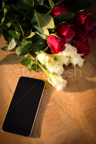 Yellow and red roses with smartphone on the wooden table Stock photo © wavebreak_media