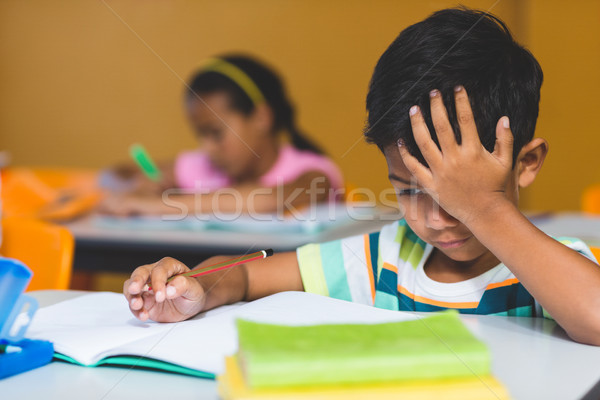 Irritated boy with head in hand looking at book Stock photo © wavebreak_media