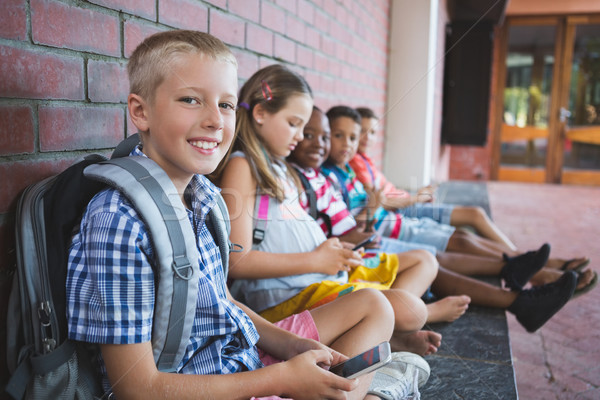 Iskolás gyerekek ül folyosó mobiltelefon iskola lány Stock fotó © wavebreak_media