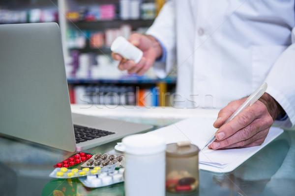 Pharmacist writing prescriptions for medicines Stock photo © wavebreak_media