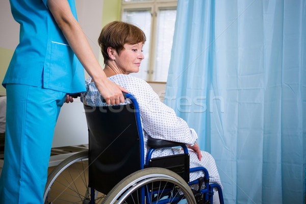Patient sitting on wheel chair with nurse standing behind Stock photo © wavebreak_media