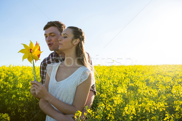 Couple holding blowing pinwheel in mustard field Stock photo © wavebreak_media