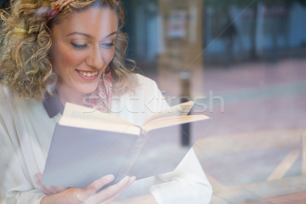 Stock photo: Smiling woman reading book seen through cafe window
