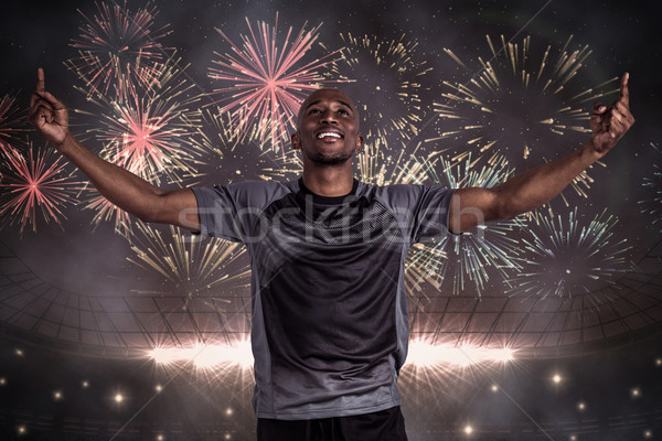 Composite image of happy sportsman with arms raised after victor Stock photo © wavebreak_media