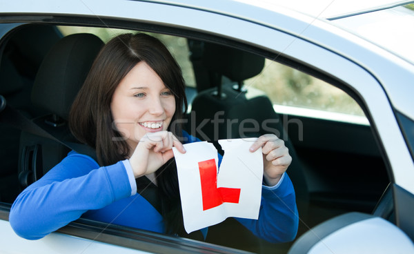 Joyful teen girl sitting in her car tearing a L-sign Stock photo © wavebreak_media