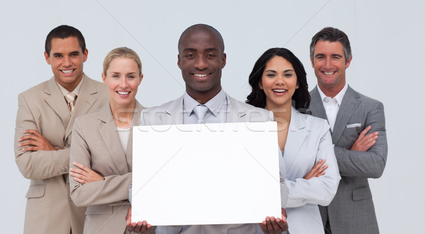 Afro-American businessman holding a white card with his team Stock photo © wavebreak_media