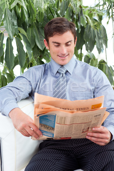 Stock photo: Attractive businessman reading a newspaper on a sofa
