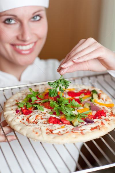 Bright female chef cooking a pizza Stock photo © wavebreak_media
