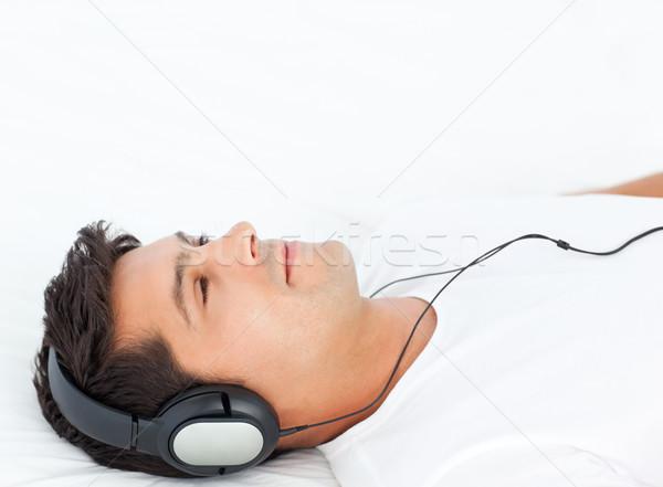 Charismatic man listening music lying on his bed Stock photo © wavebreak_media