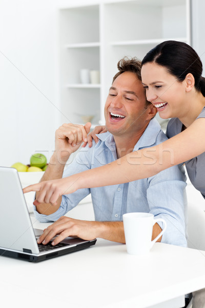 Happy woman showing something on the laptop to her boyfriend in the kitchen Stock photo © wavebreak_media