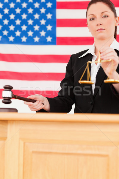 Portrait of a young judge knocking a gavel and holding scales of justice with an American flag in th Stock photo © wavebreak_media