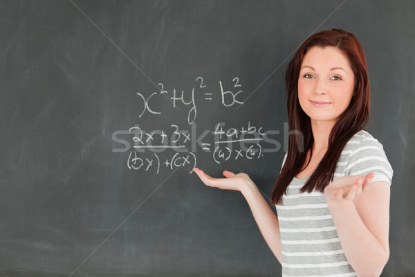 Smiling young woman solving an equation in a classroom Stock photo © wavebreak_media