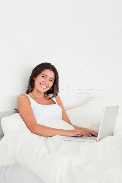 Donna sorridente notebook letto guardando fotocamera camera da letto Foto d'archivio © wavebreak_media